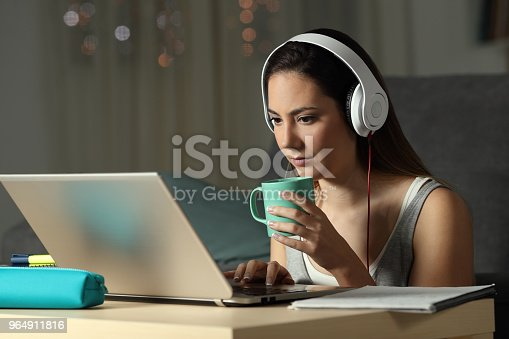 istock Student watching video tutorials in the night 964911816