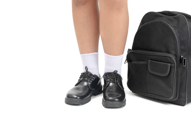 Student wear a black leather shoes and school bag. stock photo
