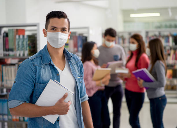 Student wearing a facemask at the library while looking at the camera stock photo