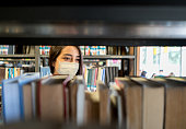 istock Student wearing a facemask at the library while looking for a book 1278100869