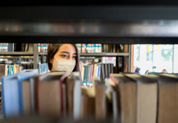 Student wearing a facemask at the library while looking for a book stock photo
