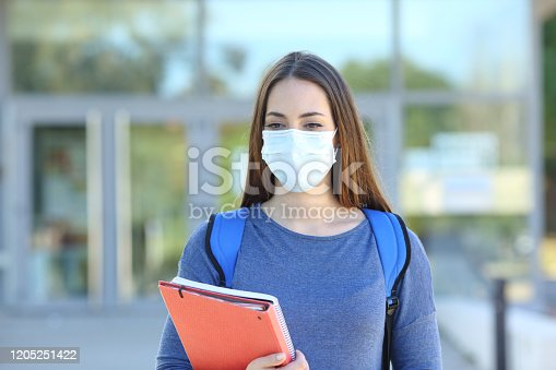 Front view of a student wearing a protective mask walking in a campus