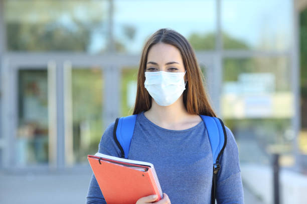 Student wearing a mask walking in a campus stock photo