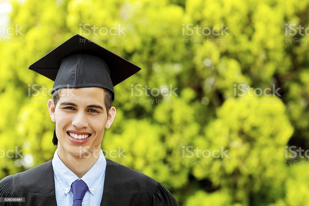 Student Wearing Mortar Board And Gown On Graduation Day stock photo