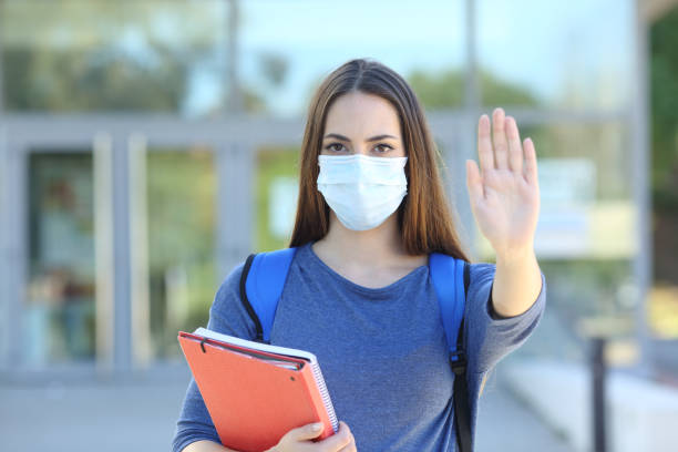 Student with a mask gesturing stop stock photo
