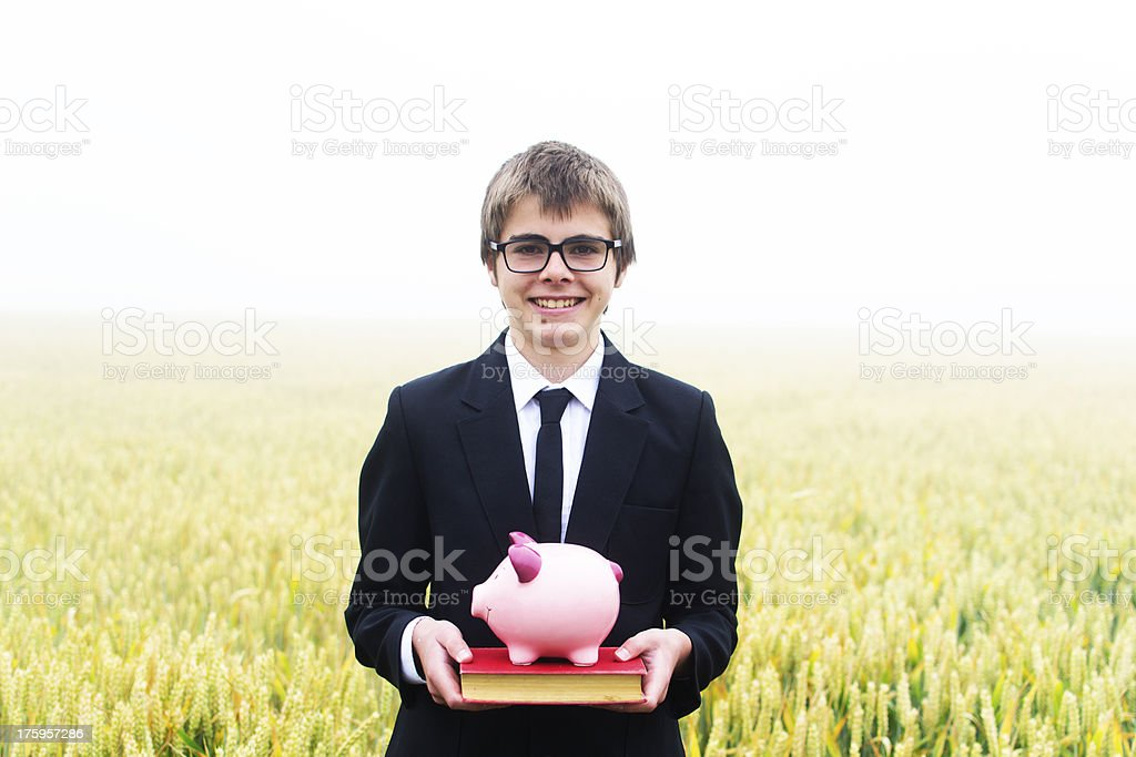 Student with a piggy bank and book stock photo