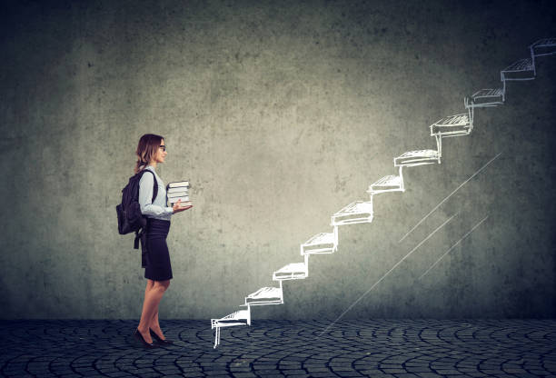 student with books standing on the stairs of education leading to success stock photo