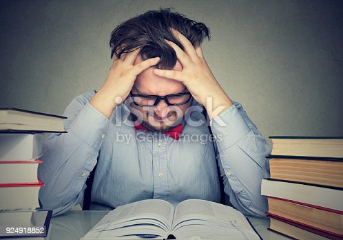 840623324istockphoto Student with desperate expression looking at his books 924918852