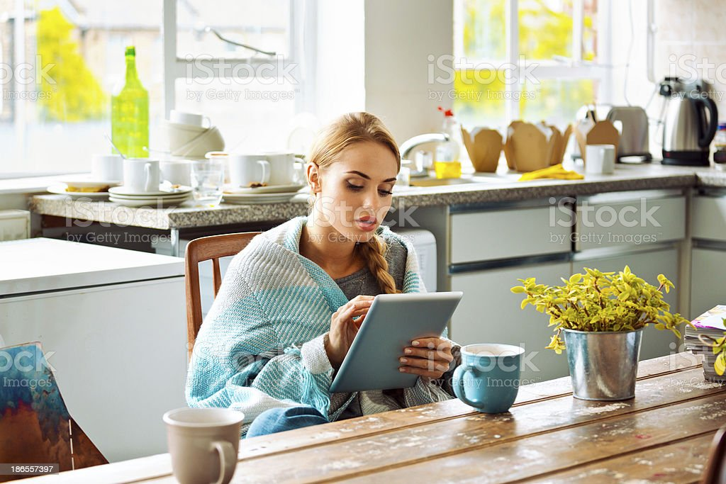 Student with digital tablet at home Young woman has a cold, sitting in a kitchen wrapped in blanket and using a digital tablet. 20-24 Years Stock Photo