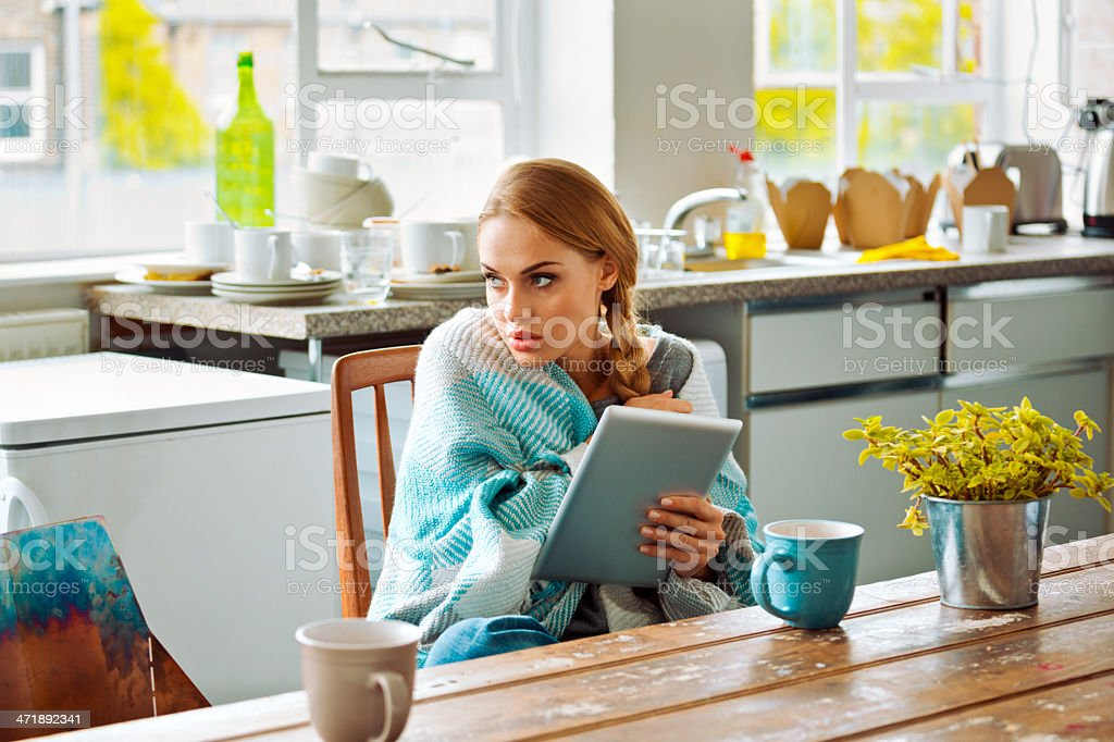 Student with digital tablet at home Young woman has a cold, sitting in a kitchen wrapped in blanket, holding a digital tablet and looking through window. 20-24 Years Stock Photo