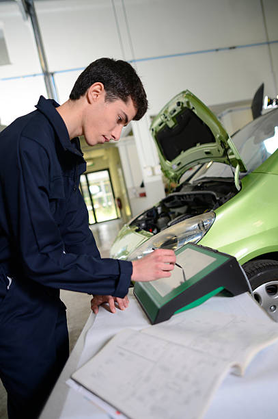 Student with dungarees using computer in garage stock photo