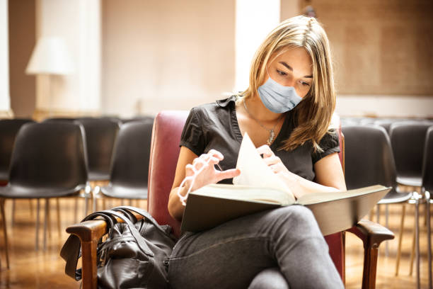 student with face mask in the library stock photo