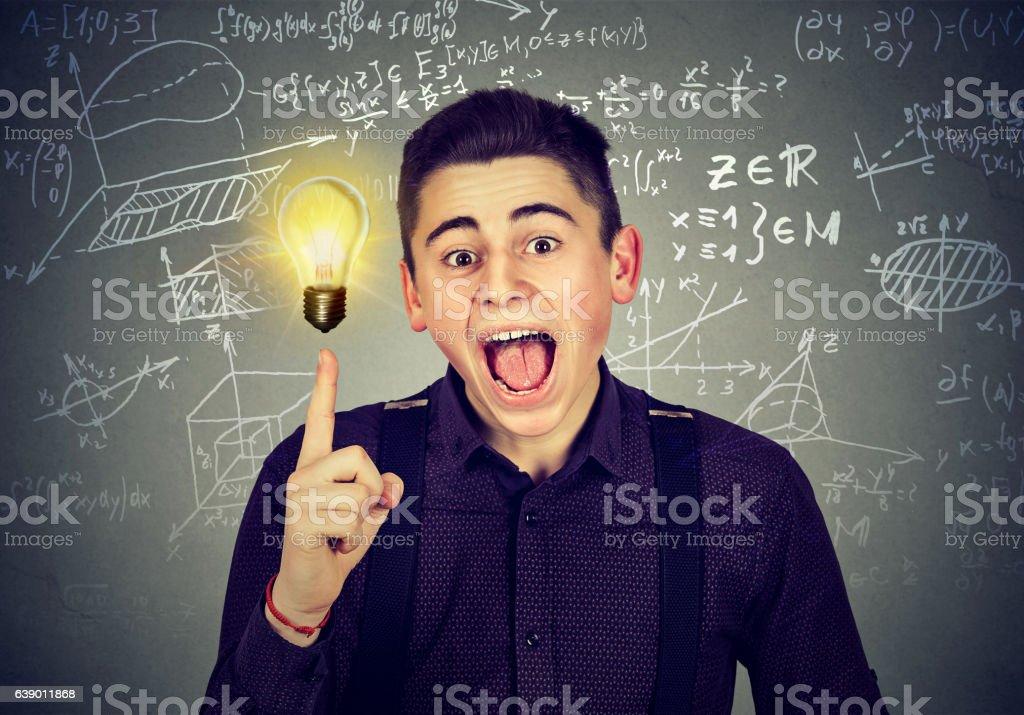 student with idea light bulb science formulas on blackboard smart student with bright idea light bulb and high school maths and science formulas on blackboard background Adult Stock Photo
