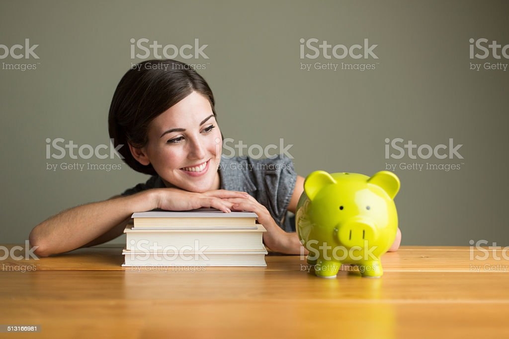 Student woman with piggy bank stock photo