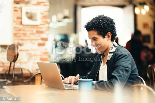 Mexican Student working on laptop in Coffeeshop.