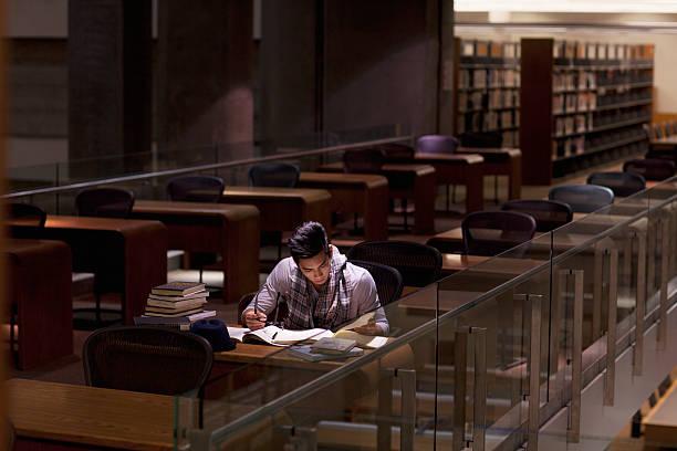 estudiantes trabajan en la biblioteca en la noche - biblioteca fotografías e imágenes de stock