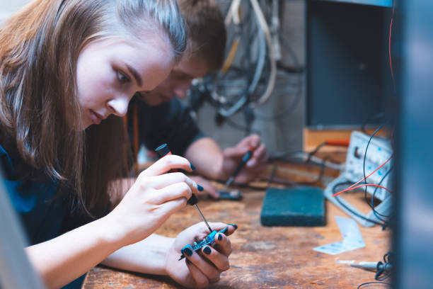 Student working in their lab together. Engineering, Student, Electronics - Two aspiring engineers screwing small components on their circuit boards for a class assignment. college fair stock pictures, royalty-free photos & images