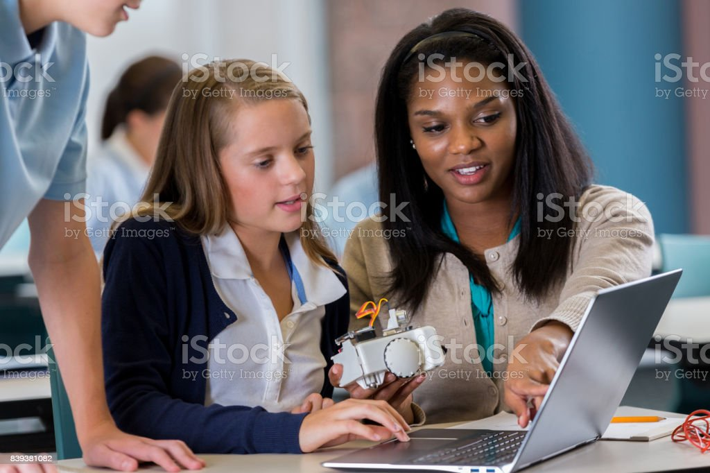 Estudiante trabaja en equipo portátil con profesor en el laboratorio de robótica - foto de stock