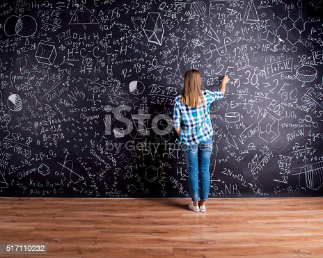 istock Student writing on big blackboard with mathematical symbols 517110232