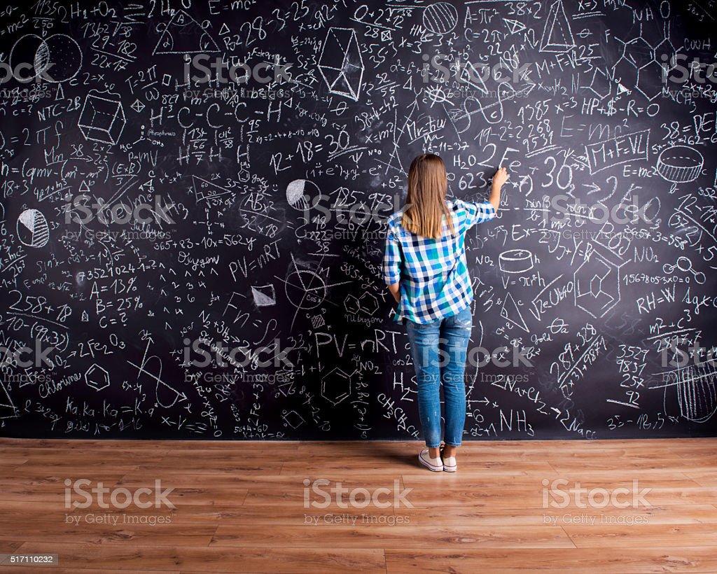 Student writing on big blackboard with mathematical symbols stock photo