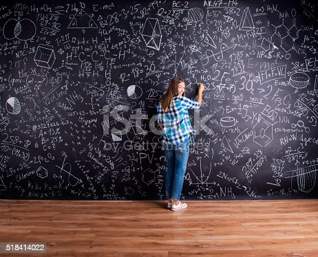 istock Student writing on big blackboard with mathematical symbols 518414022