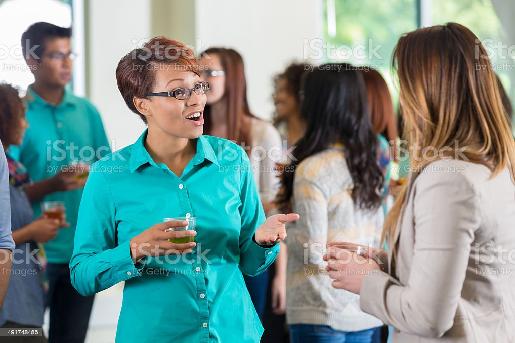Students and faculty networking during college mixer or party stock photo