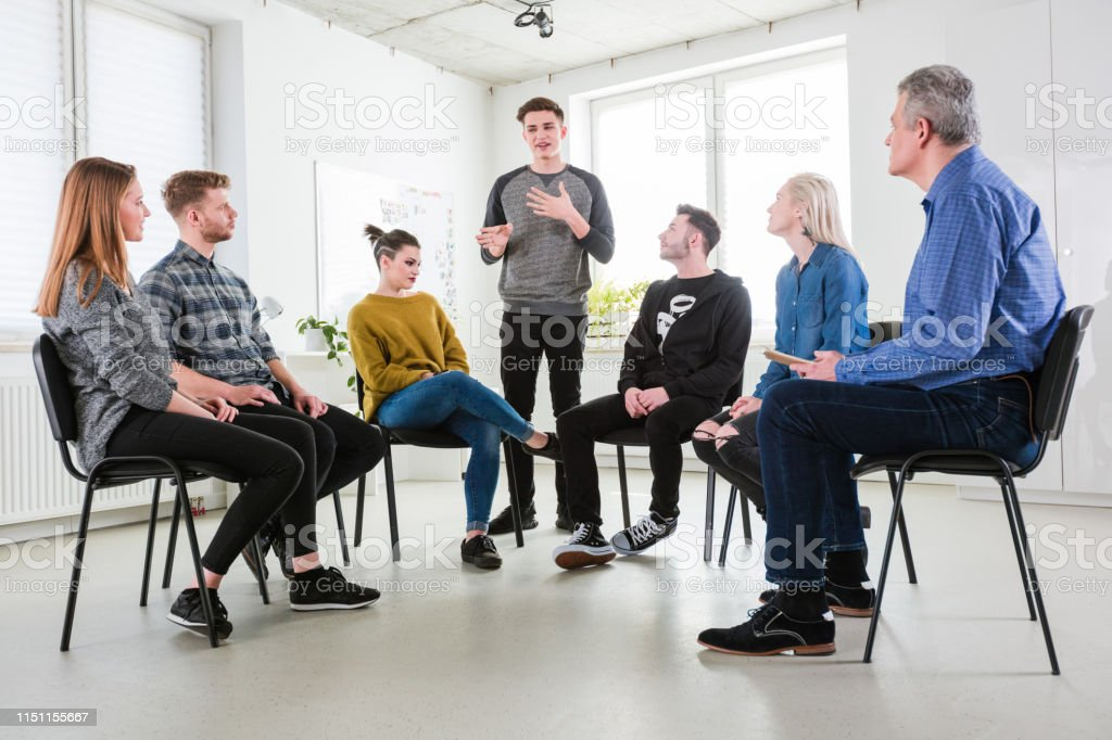 Students and social worker listening to young male Students and social worker listening to young male. Men and women are in group therapy at university. They are wearing casuals. 18-19 Years Stock Photo
