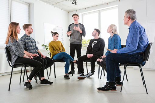 Students And Social Worker Listening To Young Male Stock Photo - Download Image Now