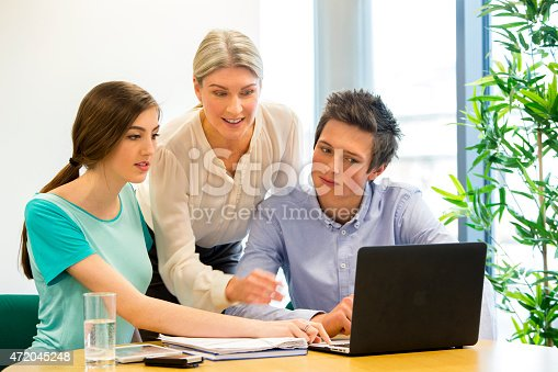 481711196istockphoto Students and teacher looking at a laptop 472045248