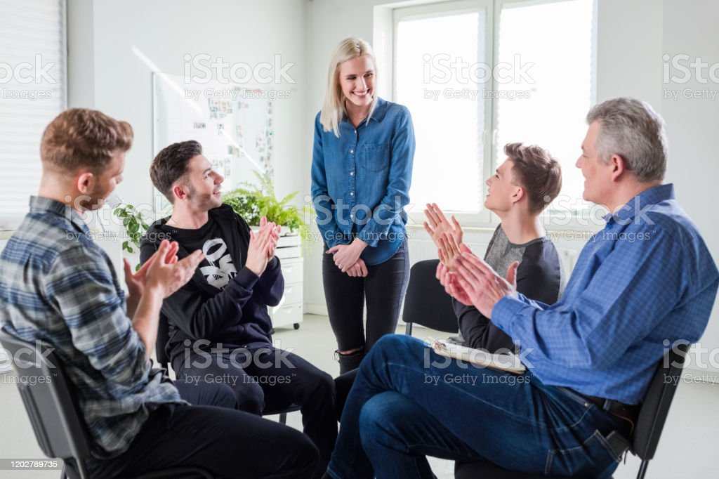 Students and therapist applauding for young woman Students and therapist applauding for smiling young woman. Female is with friends and social worker at university. They are clapping during group therapy session. 18-19 Years Stock Photo