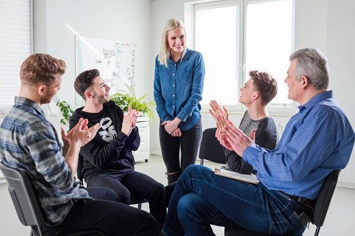Students And Therapist Applauding For Young Woman Stock Photo - Download Image Now