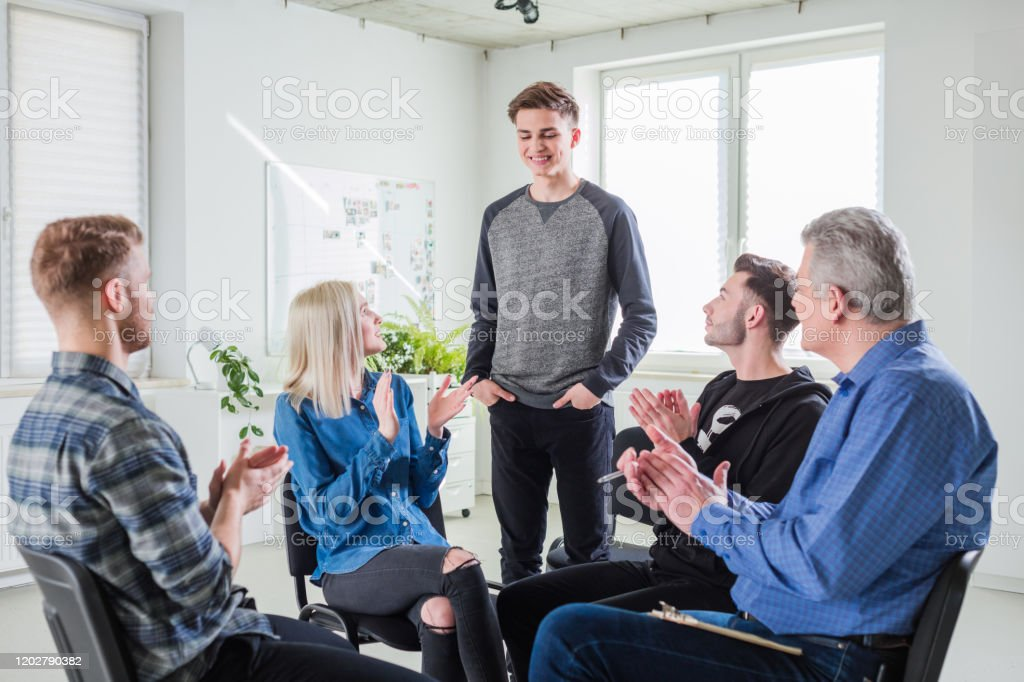 Students and therapist clapping at therapy session Happy students and social worker clapping for male during group therapy. Motivated men and women are at lecture hall. They are wearing casuals. 18-19 Years Stock Photo