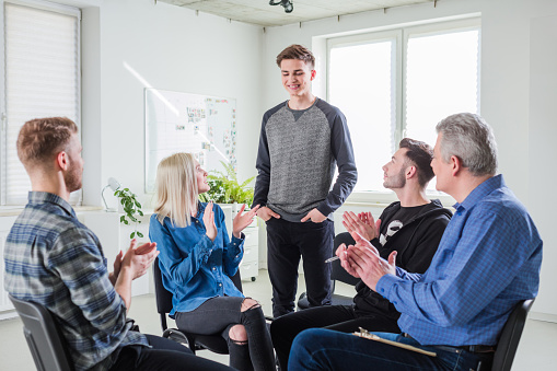 Students And Therapist Clapping At Therapy Session Stock Photo - Download Image Now