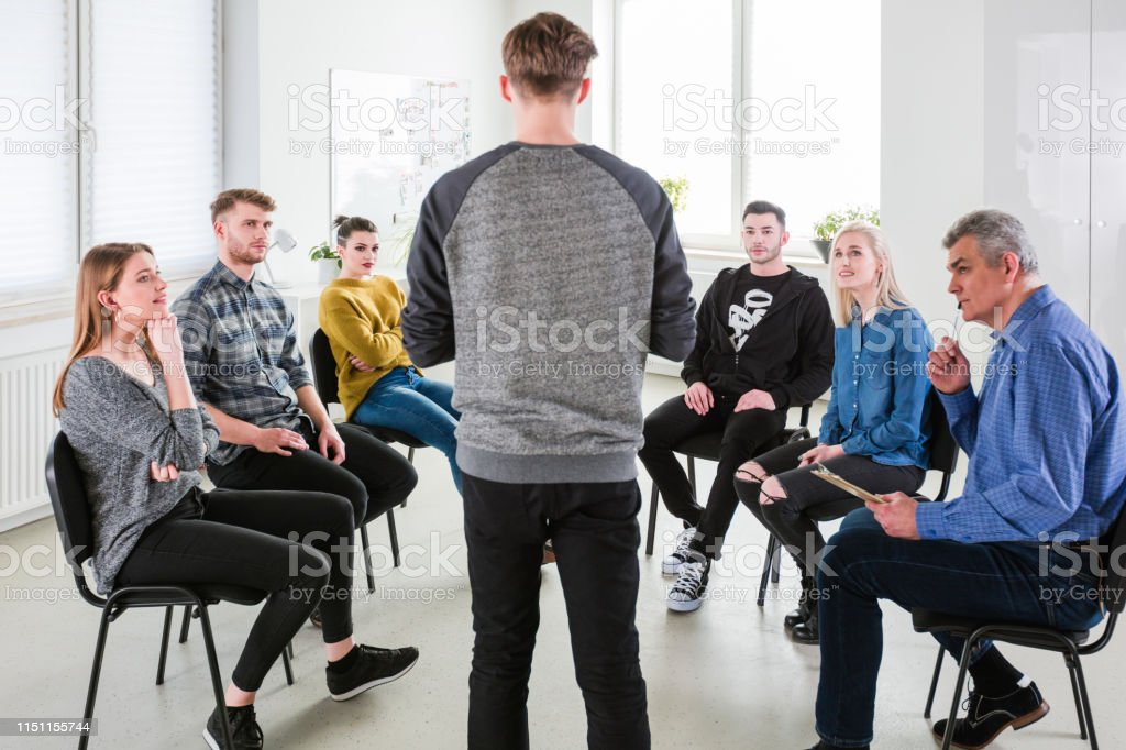 Students and therapist listening to young man Students and mental health therapist listening to young man. Group of people are in university for therapy. They are wearing casuals. 18-19 Years Stock Photo