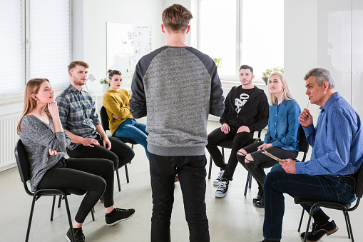 Students And Therapist Listening To Young Man Stock Photo - Download Image Now