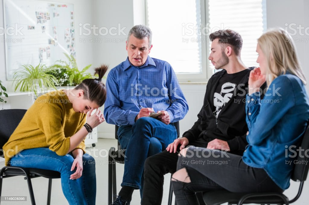 Students and therapist looking at depressed woman Students and therapist looking at depressed young woman in lecture hall. Female and male are sitting in group therapy session at university. They are in casuals. 18-19 Years Stock Photo