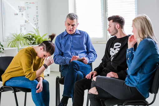Students And Therapist Looking At Depressed Woman Stock Photo - Download Image Now