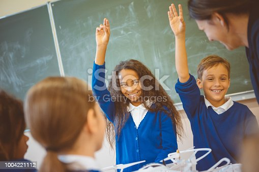 istock Students answering questions in class 1004221112