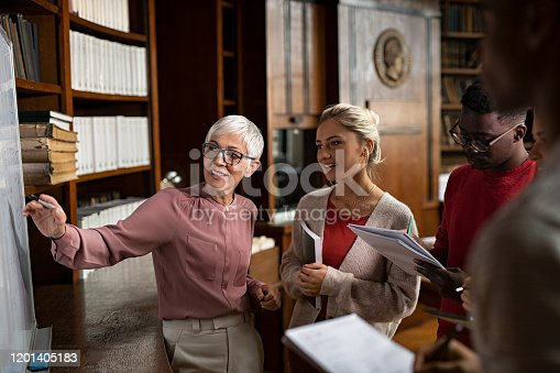 Professor helping student in library at college. Group of multiethnic students taking an active part in a lesson while standing in library. Mature woman teacher and university student discussing over math formulas on whiteboard.