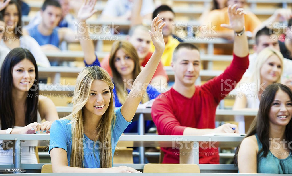Group of students sitting at the university amphitheatre with raised...