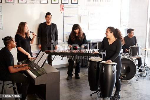 Students At Performing Arts School Playing In Band At Rehearsal With Teacher