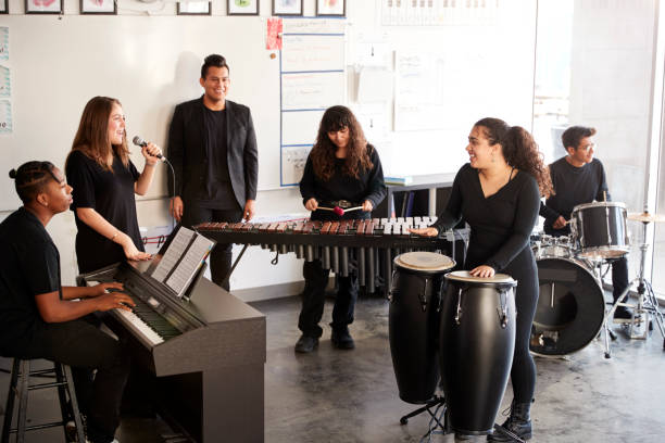 Students At Performing Arts School Playing In Band At Rehearsal With Teacher Students At Performing Arts School Playing In Band At Rehearsal With Teacher percussion instrument stock pictures, royalty-free photos & images
