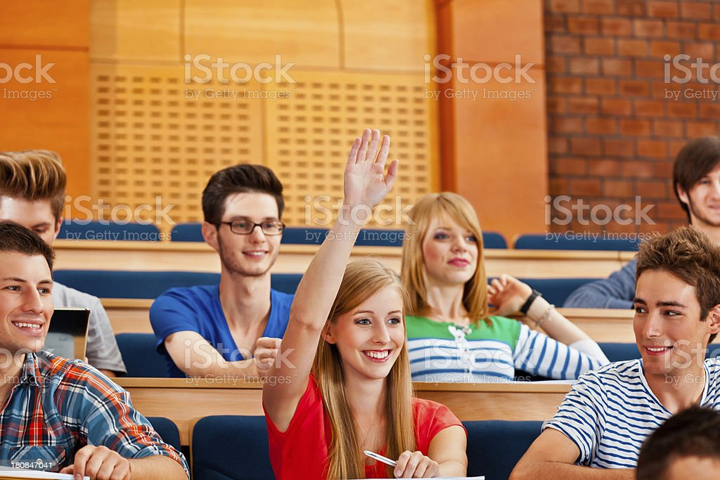 Students at the lecture College students sitting in the lecture hall at the university and listening to the lecture. The young woman in red blouse raising hand in answering gesture. 20-24 Years Stock Photo