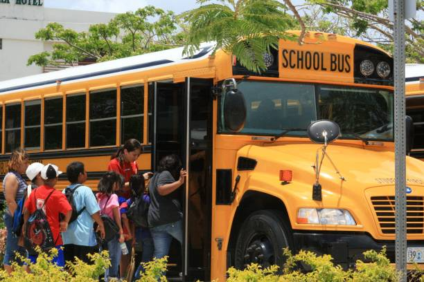 students boarding a school bus in Saipan SAIPAN, CNMI—Students and their chaperones board a school bus at a field trip in Saipan, Northern Mariana Islands in April 2015. field trip stock pictures, royalty-free photos & images