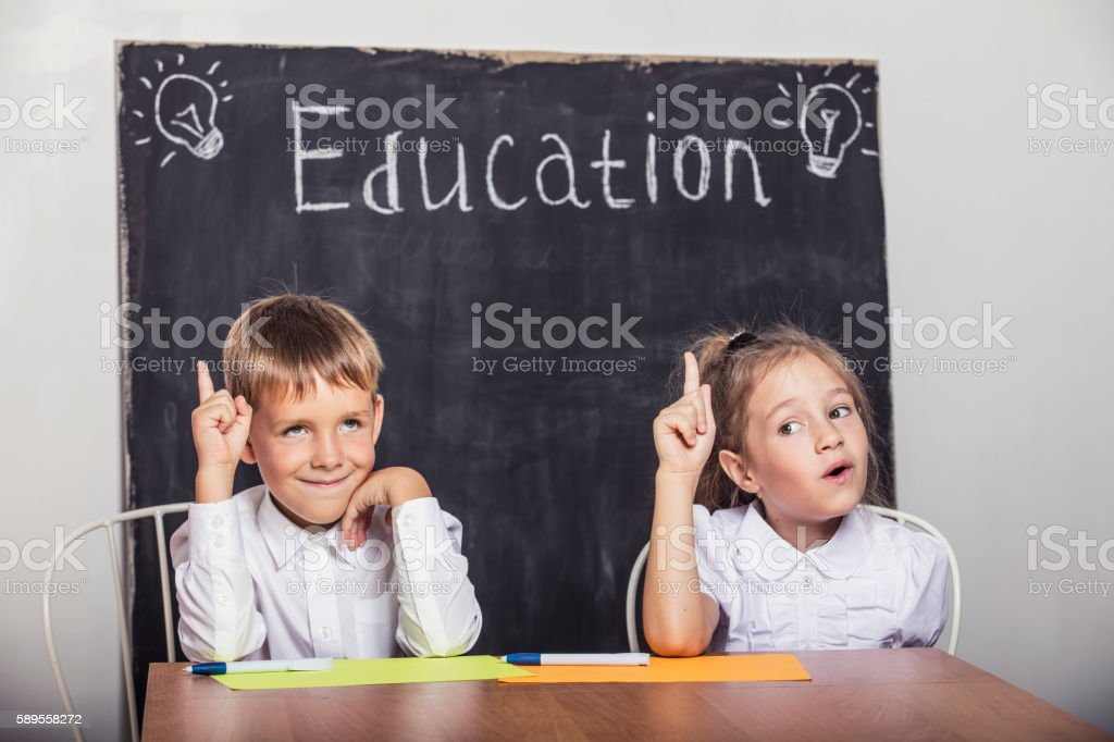 Students boy and girl at the Desk on the background stock photo