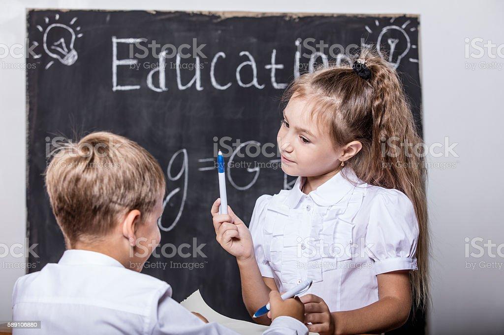 Students boy and girl on the background of the slate stock photo