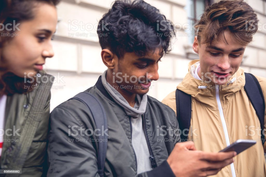 Students chatting on mobile phone stock photo