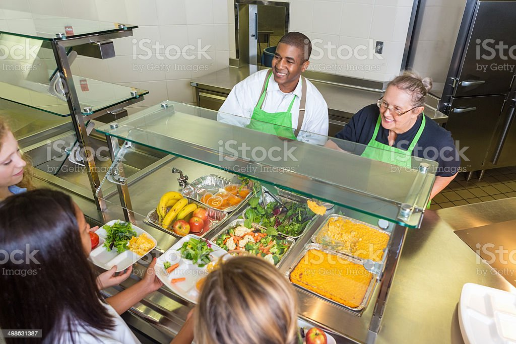 Students choosing healthy food options in school lunch line stock photo