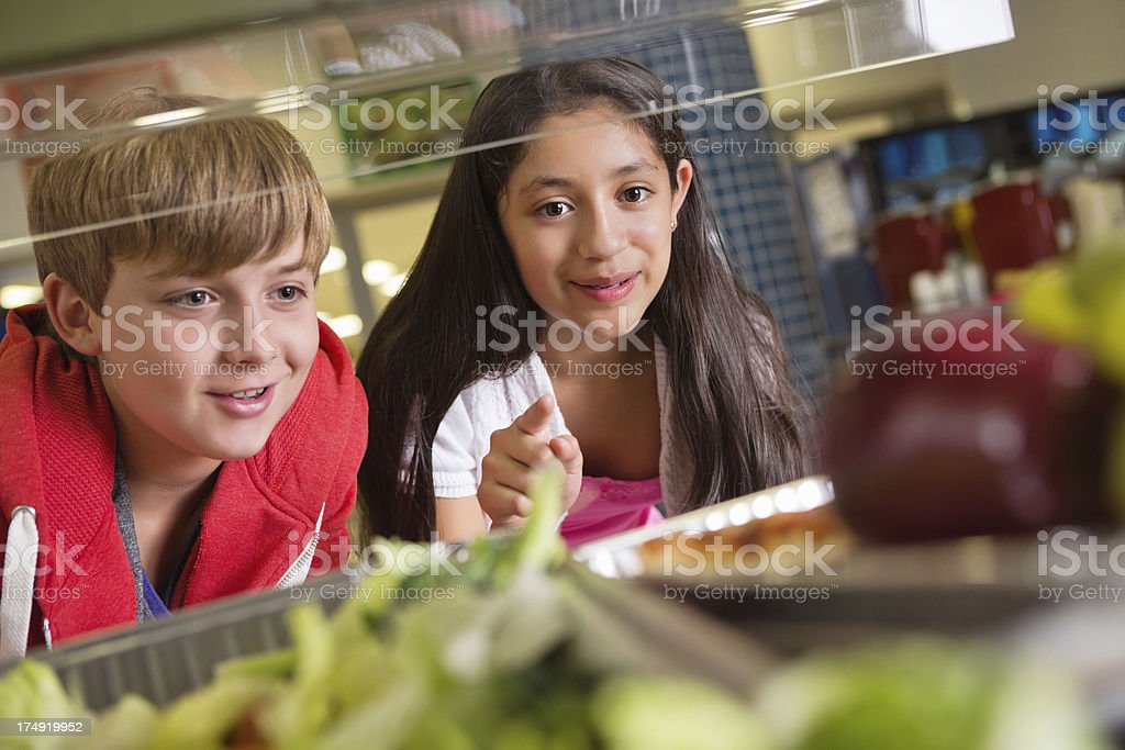 Students choosing healthy or unhealthy food in school lunch line stock photo