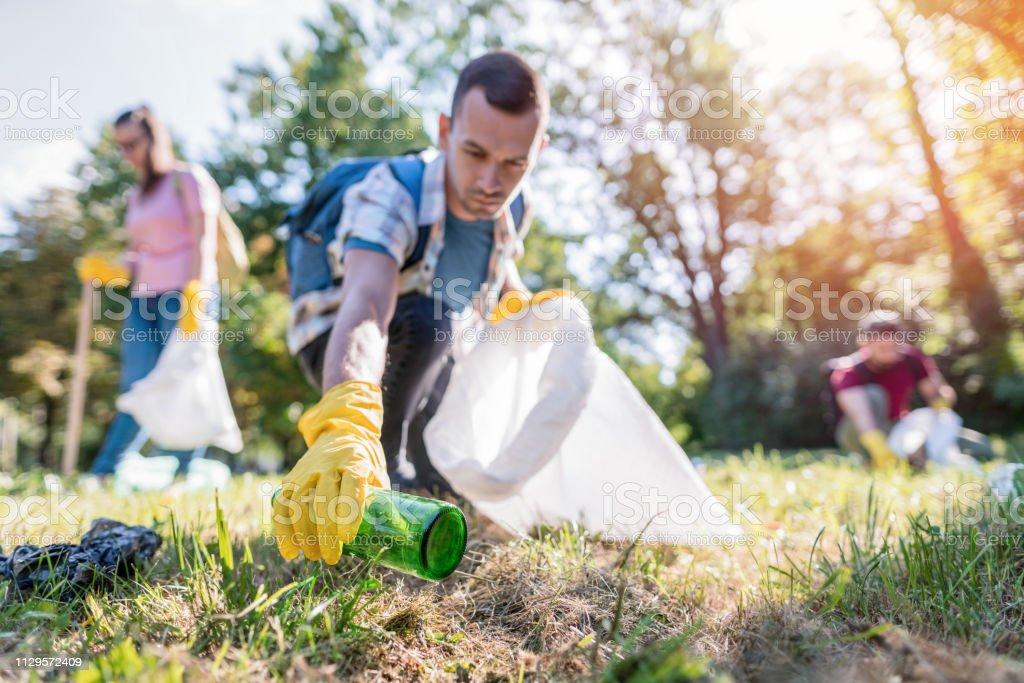 生徒達がゴミ箱から地元の公園を掃除 - 20-24歳のロイヤリティフリーストックフォト